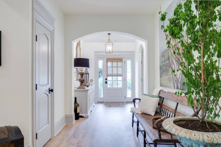 This small foyer makes up for its lack of space with brightness of the natural lights coming in form the white main door and its side lights. This is augmented by a pendant light hanging from the white ceiling.