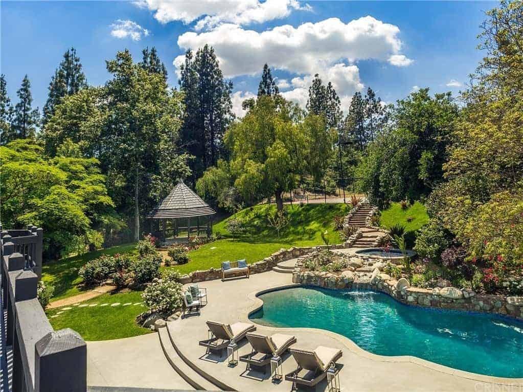 This spacious backyard is teeming with life in its green well-manicured grass, tall trees and colorful flowers that serve as a great background for the pool with lawn chairs. There is also a gazebo shaded by the trees in the distance.