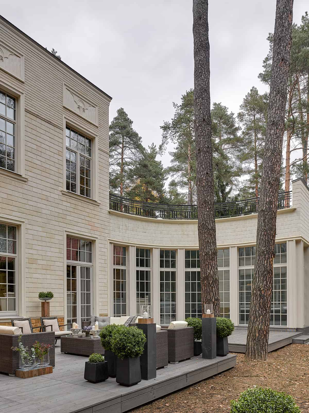 This area outside the tall windows of the house has a wooden platform over the land that has a pair of tall trees taller than the house. The sitting area is adorned with plants and shrubs in various sizes of black pots and glass vases.