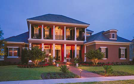 This large two story house with white pillars is given an equally majestic landscaping of well-manicured grass and a pair of medium-sized trees surrounded by reddish shrubs that pair with the terracotta walkway that is lit with lamps sticking to the ground.