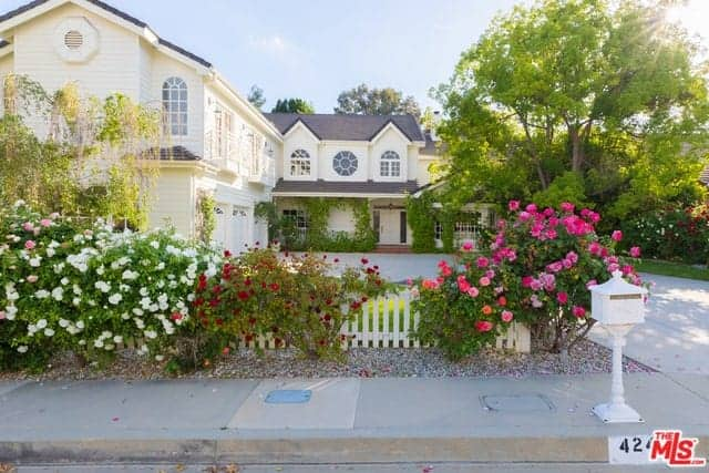 This charming view of the front of the house features a white picket fence that is adorned with various flowering plants that seem to brighten up the gray sidewalk and walkway towards the house that has a large tree beside it as well as creeping plants flanking the main door.