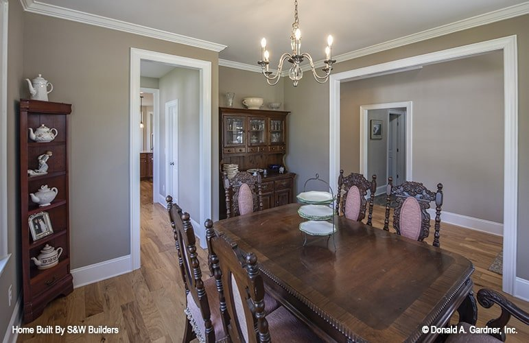 Formal dining room with hardwood flooring and gray walls accentuated with white trims. A lovely candle chandelier along with dark wood furnishings enhances the traditional charm of the room.