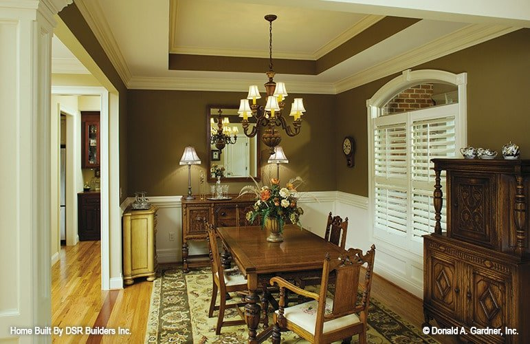 This dining room features an elegant tray ceiling and brown walls adorned with white wainscoting. Wooden furnishings and a classic area rug over hardwood flooring complete the traditional look.