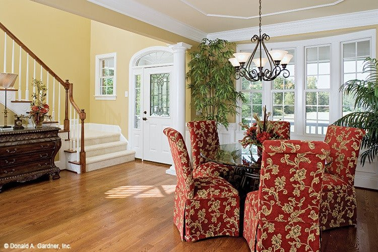 This dining room has a great view of the foyer and is furnished with a round glass top table and red skirted chairs that are reminiscent of a classic era.