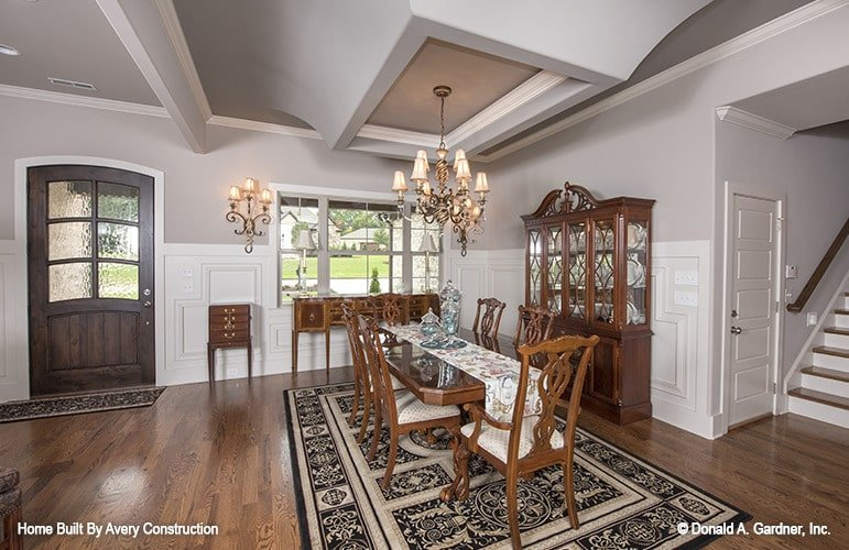 This dining room flaunts a cohesive look with its natural hardwood flooring matching with the wooden furnishings. Classic sconces and chandeliers enhance the traditional style of the room.