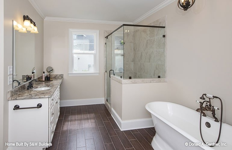 Primary bathroom with a granite top vanity, a walk-in shower, and a freestanding tub fitted with copper fixtures. The hardwood flooring adds warmth to the beige bathroom.
