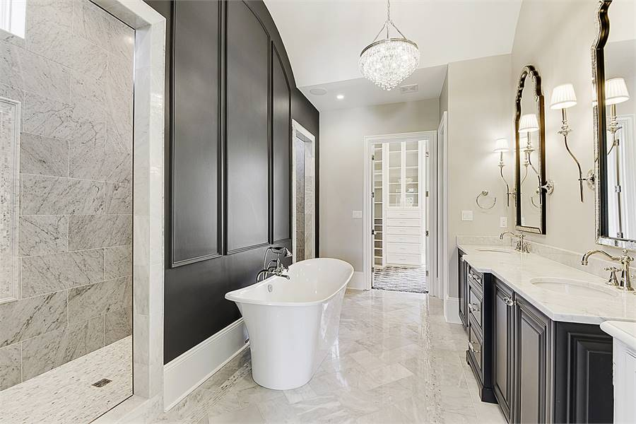 This primary bathroom oozes with elegance boasting black wainscoted walls, luxury furnishings, and marble tiled flooring that's mirrored in the walls of the spacious walk-in shower.