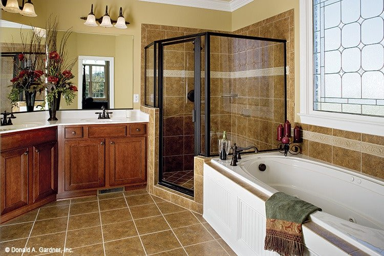 Tiled flooring that extends to the tub and shower backsplash enhances the classic look of this traditional primary bathroom.