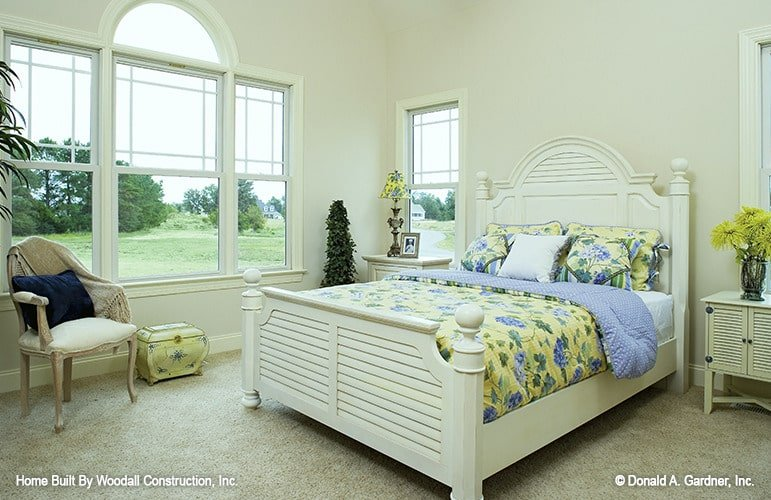The subtle yellow accents intensify the feminine charm in this primary bedroom. White furnishings, carpet flooring, and a wonderful Palladian window complete the look.
