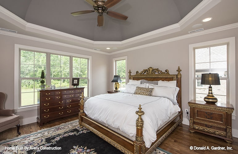 This primary bedroom features a wooden bed graced with intricate detailing. It is mirrored in the nightstands topped with traditional table lamps.
