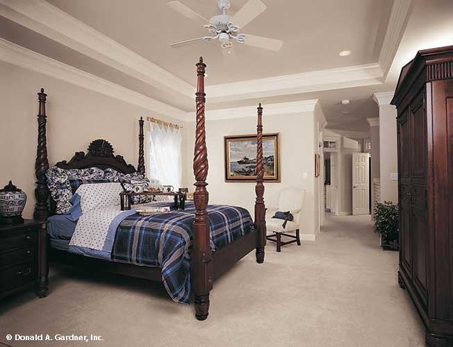 Dark wood furnishings in this primary bedroom create a stunning contrast to the beige walls, carpet flooring, and a graceful tray ceiling.