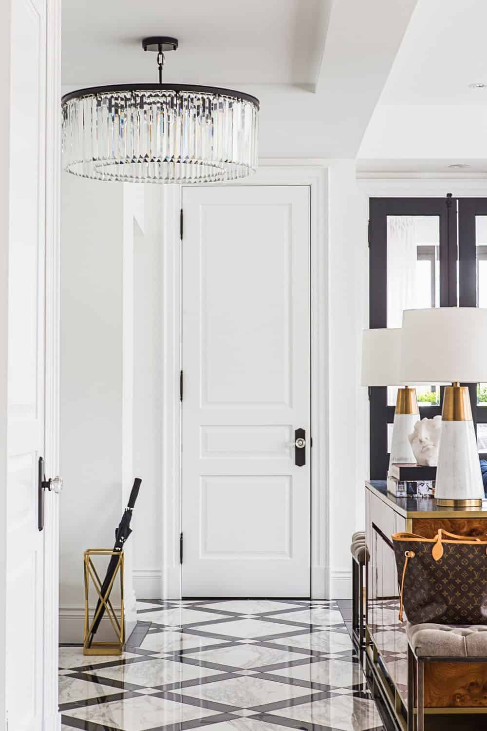 The crystal semi-flush light mounted on the white tray ceiling is the highlight of this small foyer that has a white door that blends with the white walls adorned by a golden umbrella storage on the side of the black and white patterned floor.