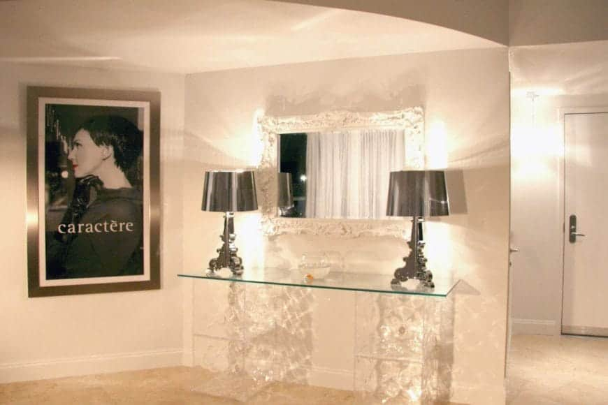Upon entry of this bright foyer, there is a console table on the side that has crystal pedestals and a glass top that supports a couple of silver modern table lamps flanking a white mirror beside a wall-mounted photograph of a woman.