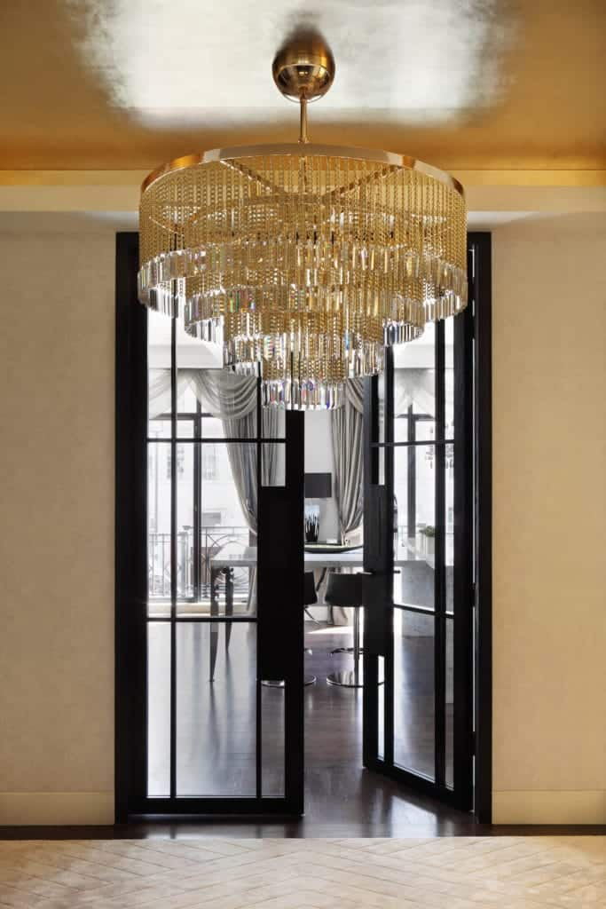 The highlight of this simple foyer is the crystal semi flush light mounted on the sleek ceiling that is complemented by a white carpeted flooring leading the way to the French glass doors that has black frames contrasting the light walls.