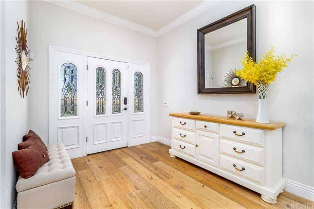 This foyer has a warm welcome with its light hardwood flooring that matches the wood top of the drawers on the side that also serves as a console table for the decors and the wall-mounted mirror across from the cushioned bench.