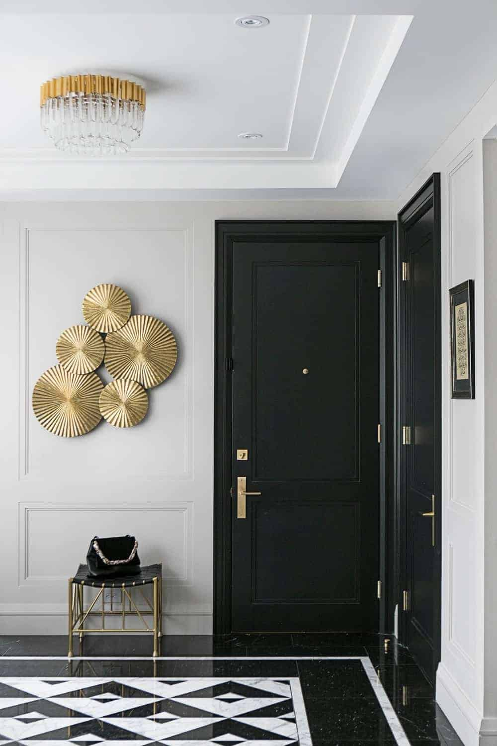 This simple foyer counterbalances its lack of floor size with an ample supply of elegance in its black white patterned marble flooring paired with the black door contrasted by the white tray ceiling. The gold elements in this foyer serve to augment the black and white contrast.