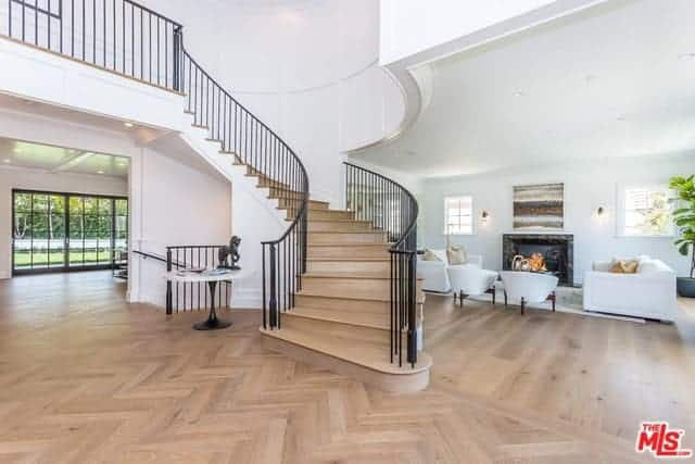 This is a grand foyer with herring bone patterns on its hardwood flooring that opens up to the living room right by the winding staircase that has wooden steps paired with black wrought iron railings that contrast the white walls.