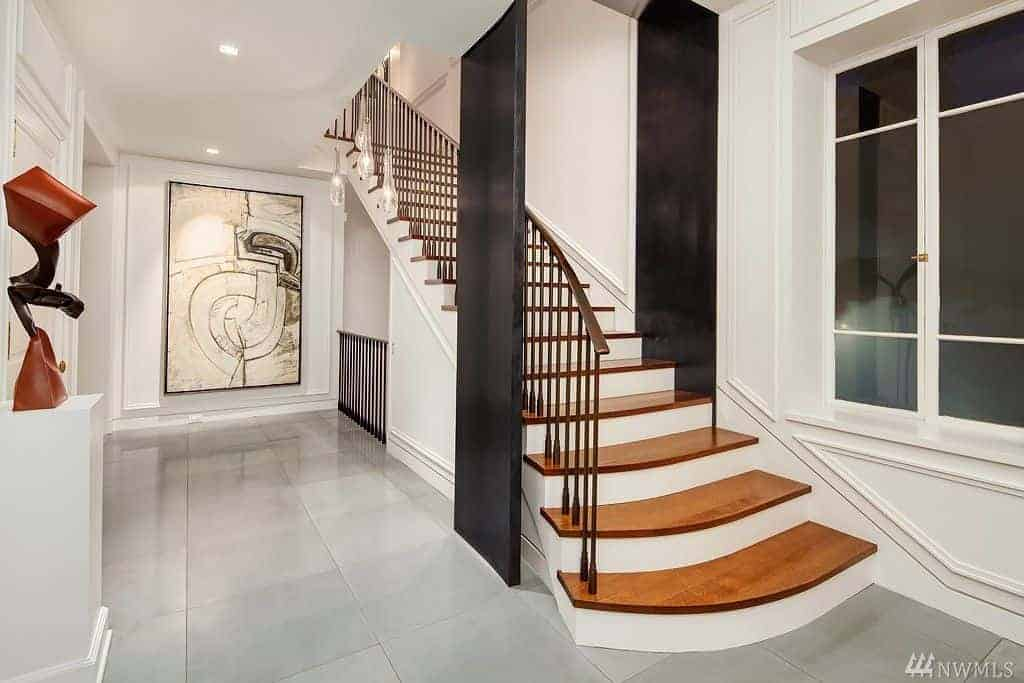 Upon entry of this bright foyer, you will feel like you stepped into an art gallery with its sculpture on a white pedestal and a large framed painting mounted on the far wall. The stairs is adorned with a couple of black panels on either side.