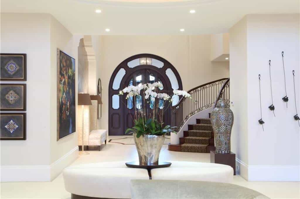 This grand and elegant foyer has a large wooden main doors that has an arched side lighting and transom window with a dark hue that stands out against the beige high walls illuminated by the standing lamp on the side of the cushioned high-backed bench on the side.