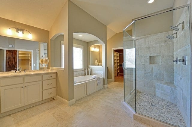This is a spacious and luxurious bathroom that has a large glass-enclosed shower area. Across from this is the bathtub that is placed in a charming alcove by the window beside the beige vanity.