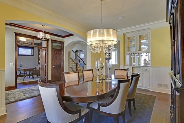 This formal dining area has inset cabinetry and a dark wood dining set lit by a crystal drum chandelier. Its hardwood flooring is mostly covered by a gray area rug that matches well with the cushions of the dining chairs.