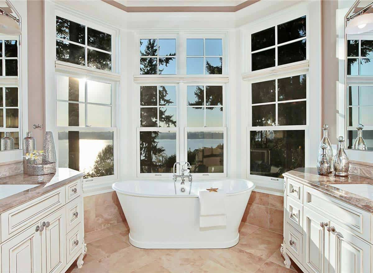 This bathroom presents a scenic view outside the tall white windows above the freestanding bathtub. This matches with the bright white vanities that stand out against the beige marble flooring tiles of the bathroom.