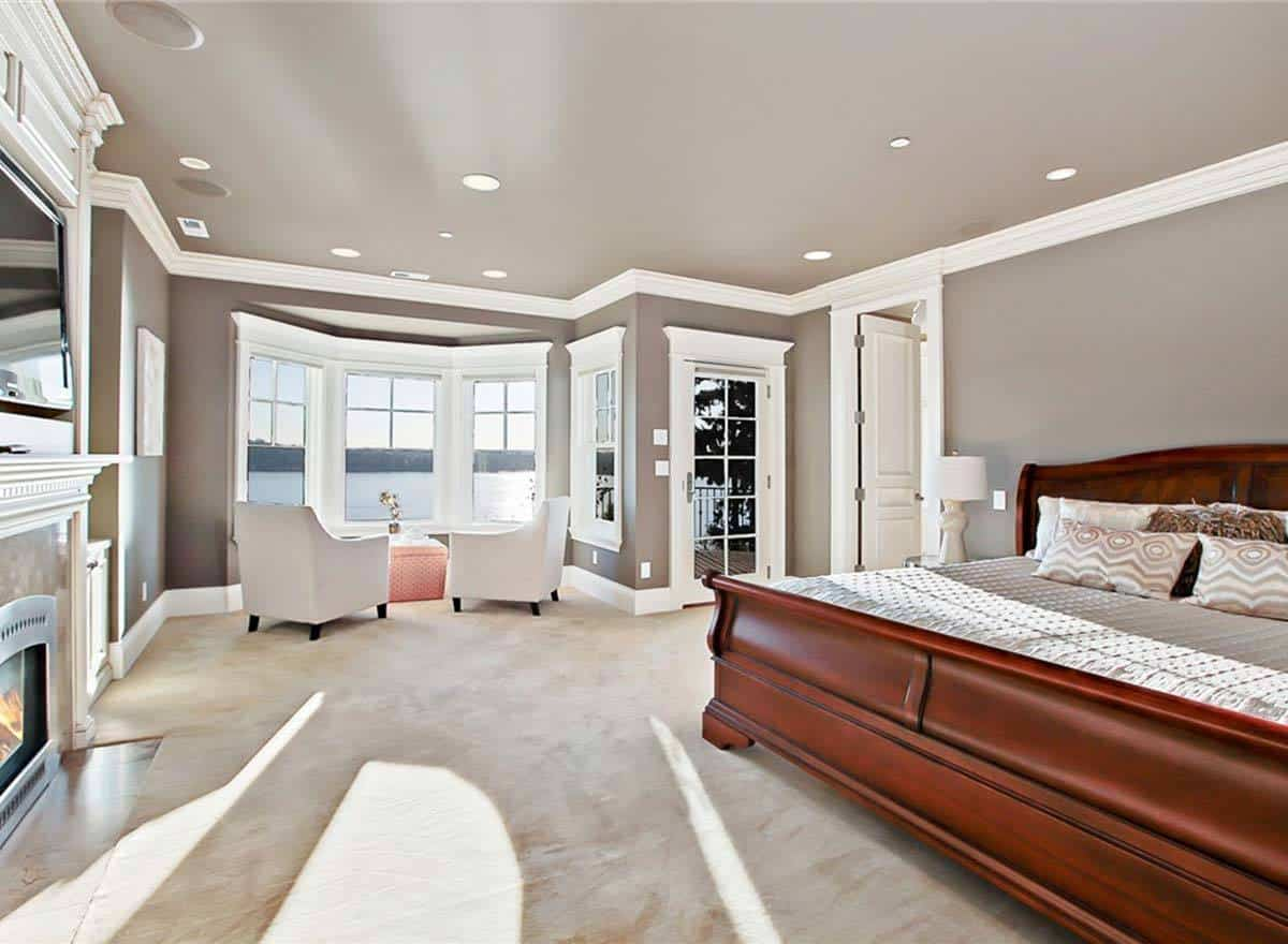 The large dark wooden sleigh bed stands out against the warm gray walls and ceiling. On the far side of this bedroom is a comfortable sitting area with a couple of cushioned armchairs facing the tall windows.
