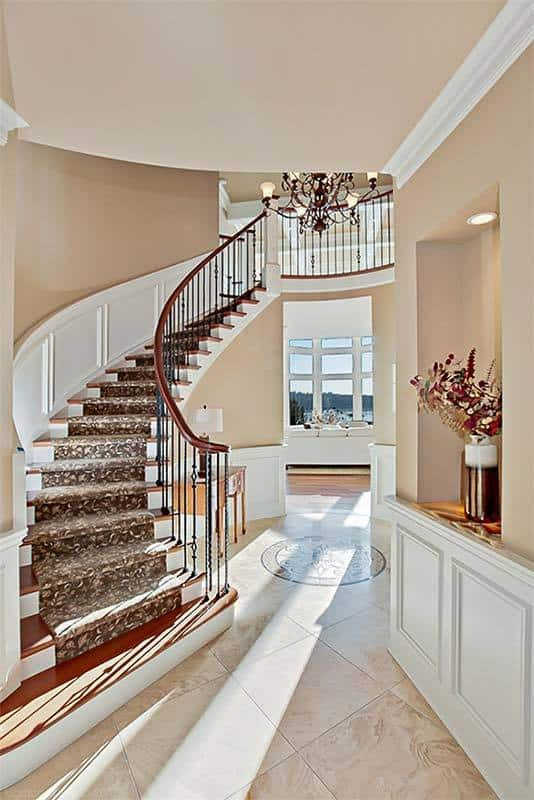 The foyer has an inset shelf, winding staircase and an ornate chandelier that hangs over the marble tiled flooring with a charming crest next to the console table.