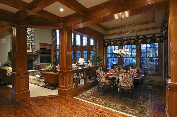 This is the dining area behind the living room that's framed with wooden columns. It is filled with cushioned seats and a round dining table illuminated by a warm chandelier hanging from the tray ceiling.