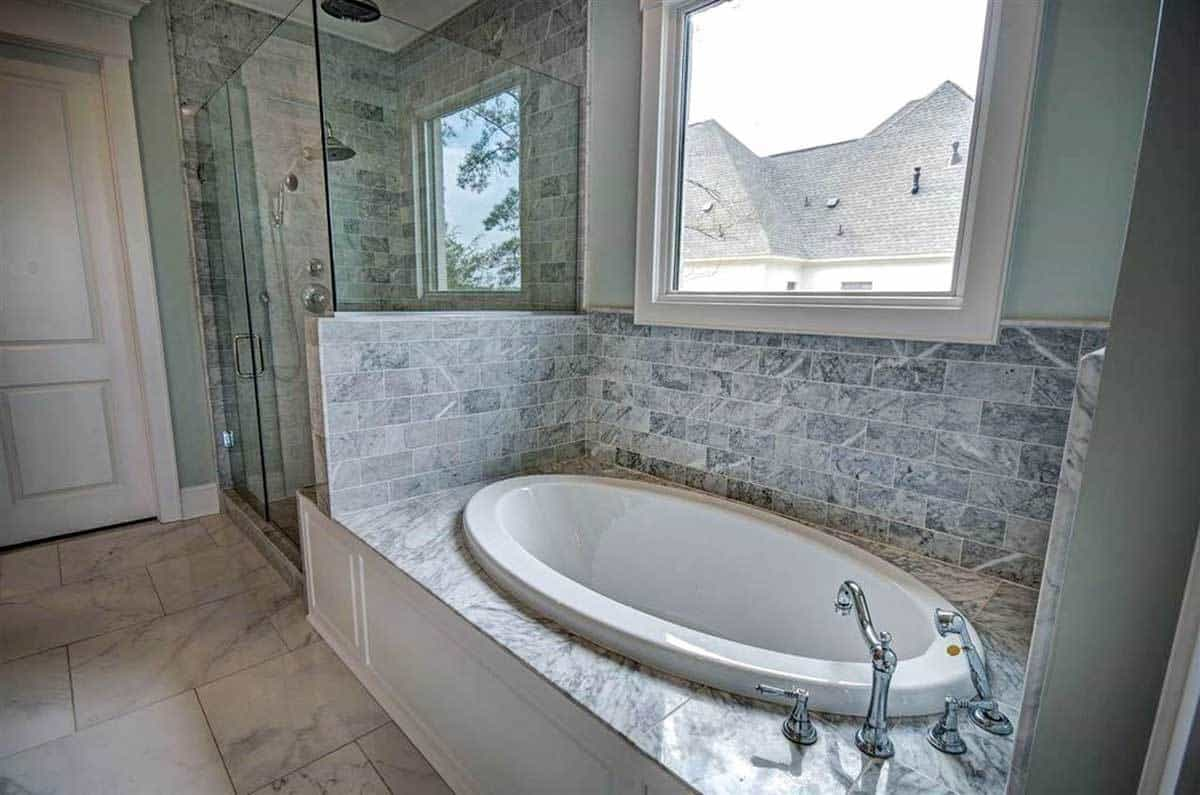 This primary bathroom has a bathtub inlaid with gray marble tiles that extend to the backsplash under the window. Beside this is the glass-enclosed shower area with the same gray marble tiles.