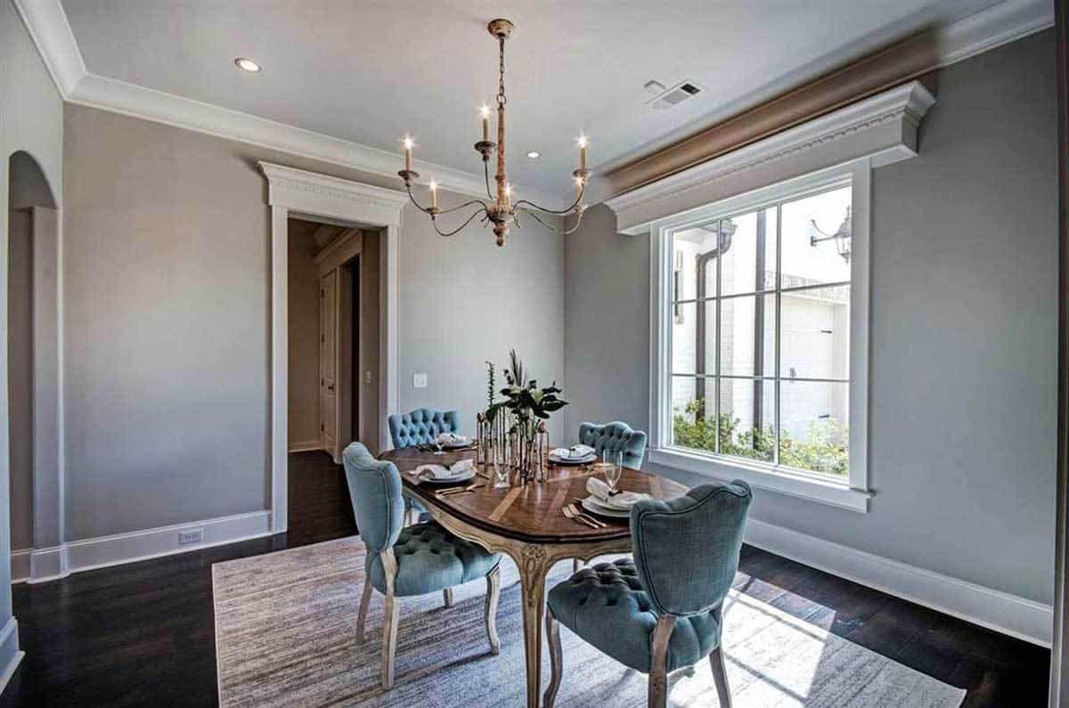 This is the formal dining room of the house with a dark wooden dining table to match the hardwood flooring that is mostly covered with an area rug. These make the pastel tones of the cushioned dining chairs stand out.
