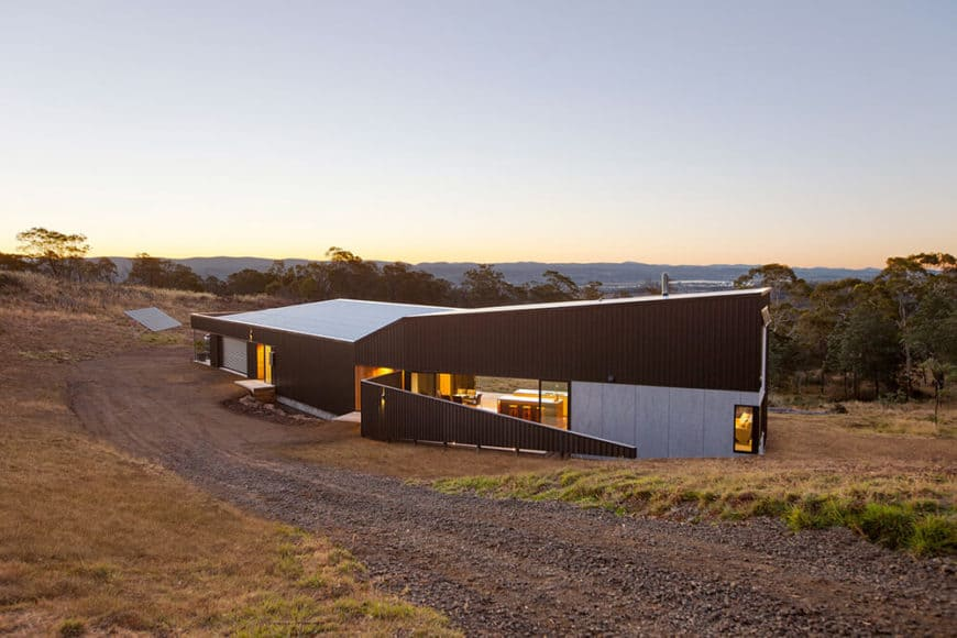 A modern house with a black exterior. This home offers a panoramic view of the breathtaking surroundings.