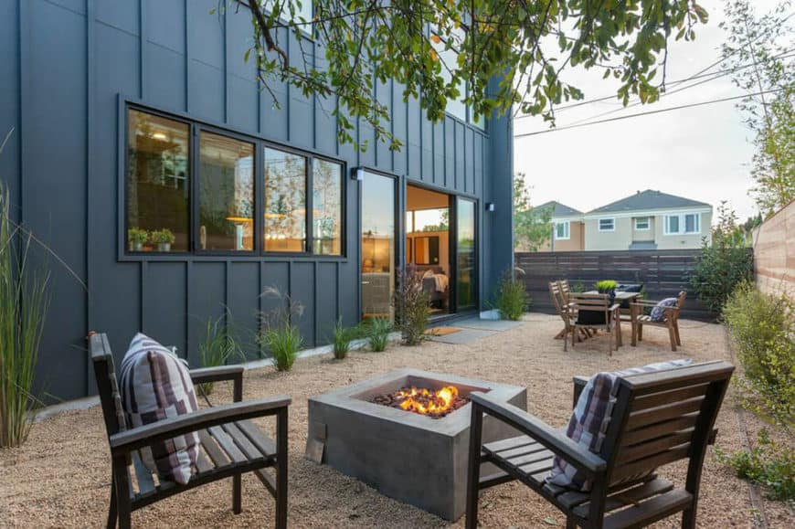 A modern home with a black exterior and a gorgeous interior, along with a relaxing outdoor area featuring sitting lounges and an outdoor dining.