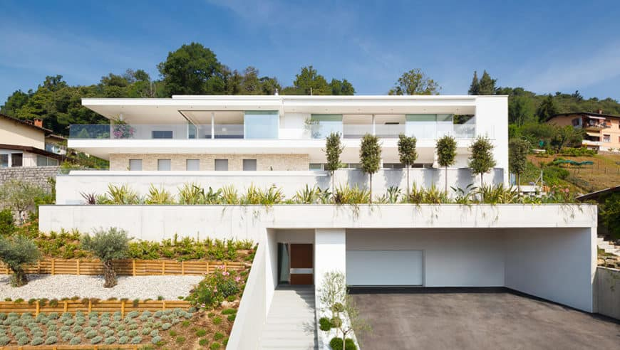 A white contemporary house featuring lots of plants along with a wide driveway and garage.
