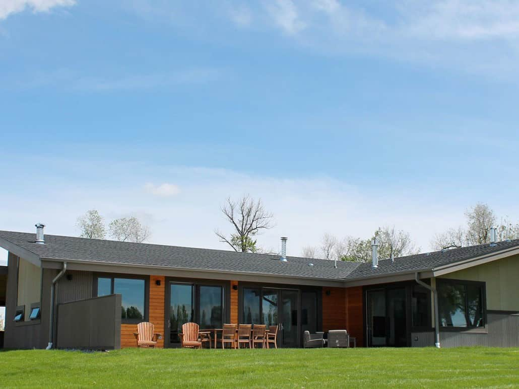 This home boasts a sprawling and well-maintained lawn area along with a black exterior.
