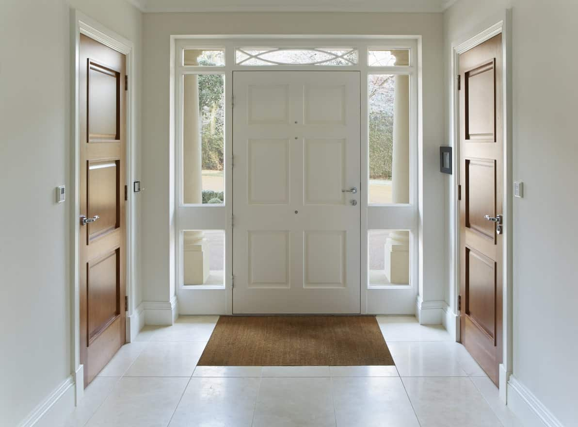 This is a charming white foyer with a white wooden traditional door with matching sidelights and a thin transom window above giving the door a nice glass frame that brings in natural light. This illuminates the white flooring and white walls.