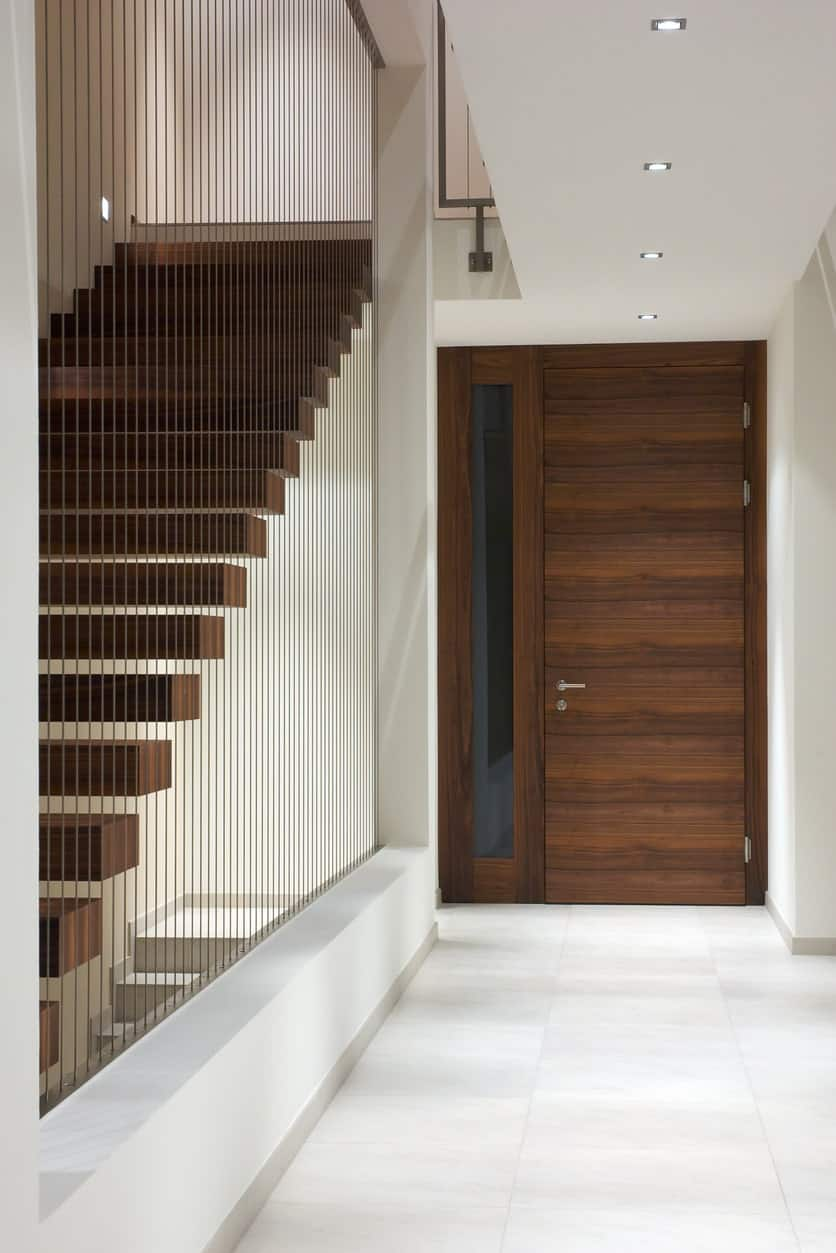 This is a simple and plain white foyer that emphasizes the wooden hues of the main door and its single sidelight with the same wooden frame. The white ceiling has a row of modern pin lights running through the middle to bring illumination to the white walls and flooring.