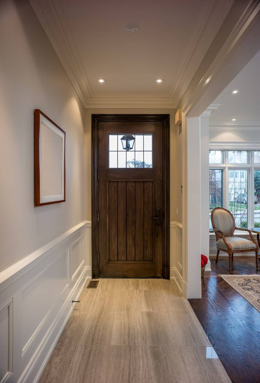 This simple and small white foyer has a charming wooden door that has a small built-in window at the top. The rustic appearance of this wooden door contrasts the elegant white wooden finish of the walls and the white tray ceiling.