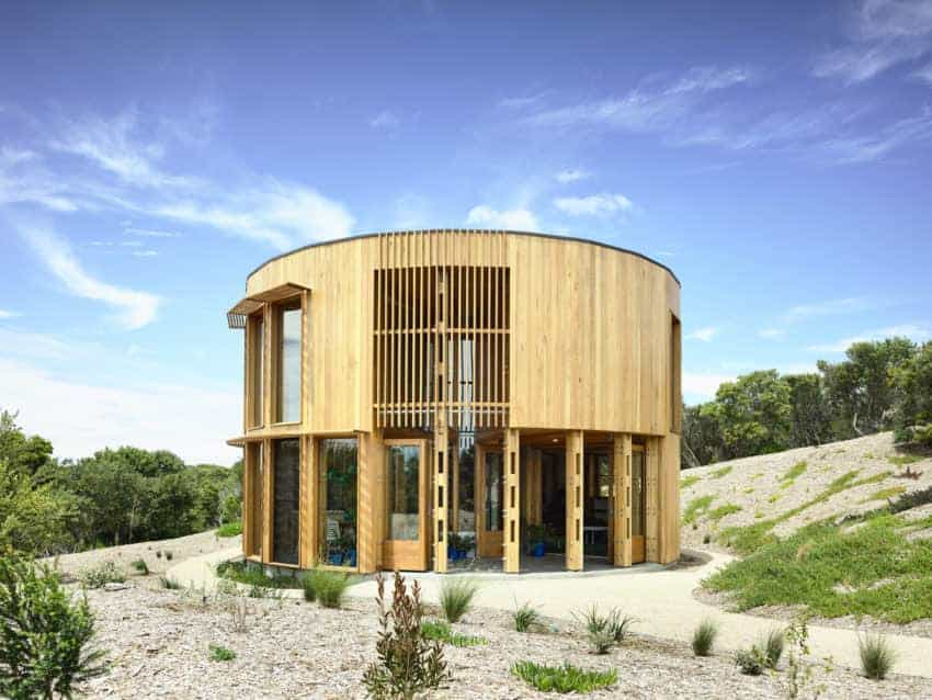 A stunning contemporary beach house with a wooden exterior and has a round design.