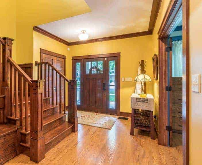 A simplistic foyer featuring a yellow and brown color scheme. Both the doors and staircase are made of wood.
