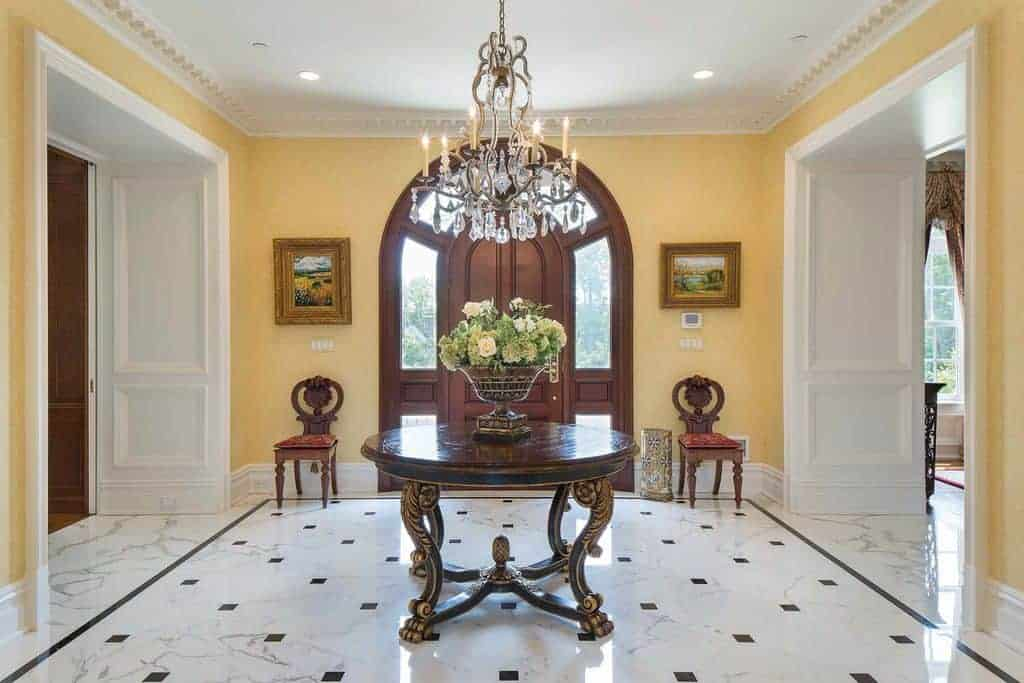 This foyer boasts classy marble tiles flooring with a fancy centerpiece table in the middle, set just beneath the gorgeous chandelier.