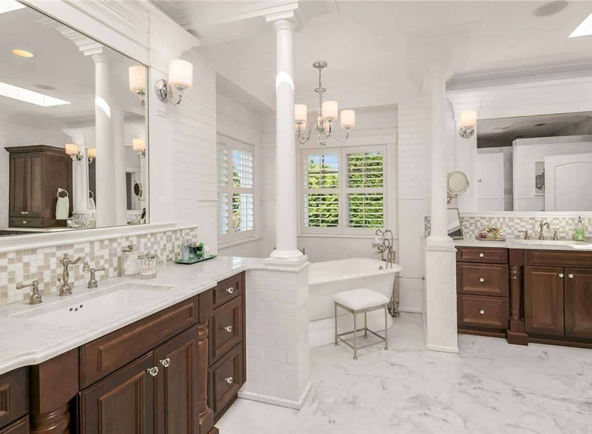 This large bathroom with an alcove for the freestanding bathtub at the corner with windows, pillars and a chandelier. This area is flanked by two vanities with dark wooden cabinetry that stands out against the light tones of the flooring.