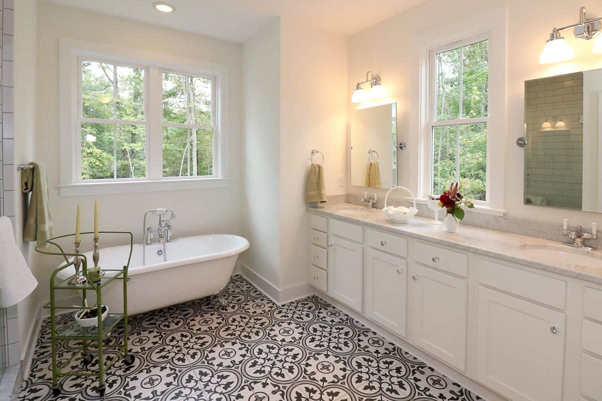 This primary bathroom has intricate flooring tiles to set a nice background for the plain white freestanding bathtub and the cabinetry of the vanity beside it.