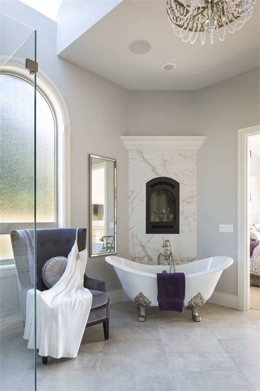 This spacious bathroom has a freestanding white porcelain bathtub beside the modern fireplace inlaid with white marble.