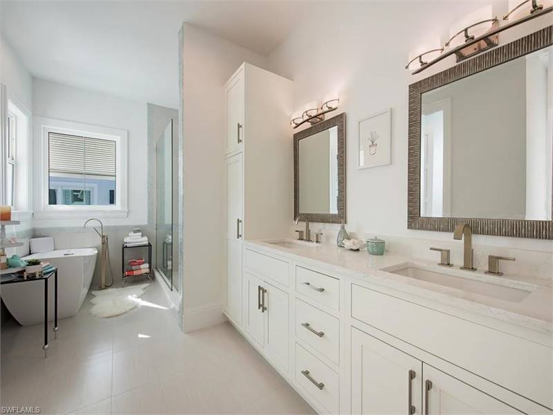 This is a simple yet lovely primary bathroom with a walk-in shower, freestanding tub, and a dual sink vanity paired with stylish framed mirrors that are topped with wall-mounted lamps.
