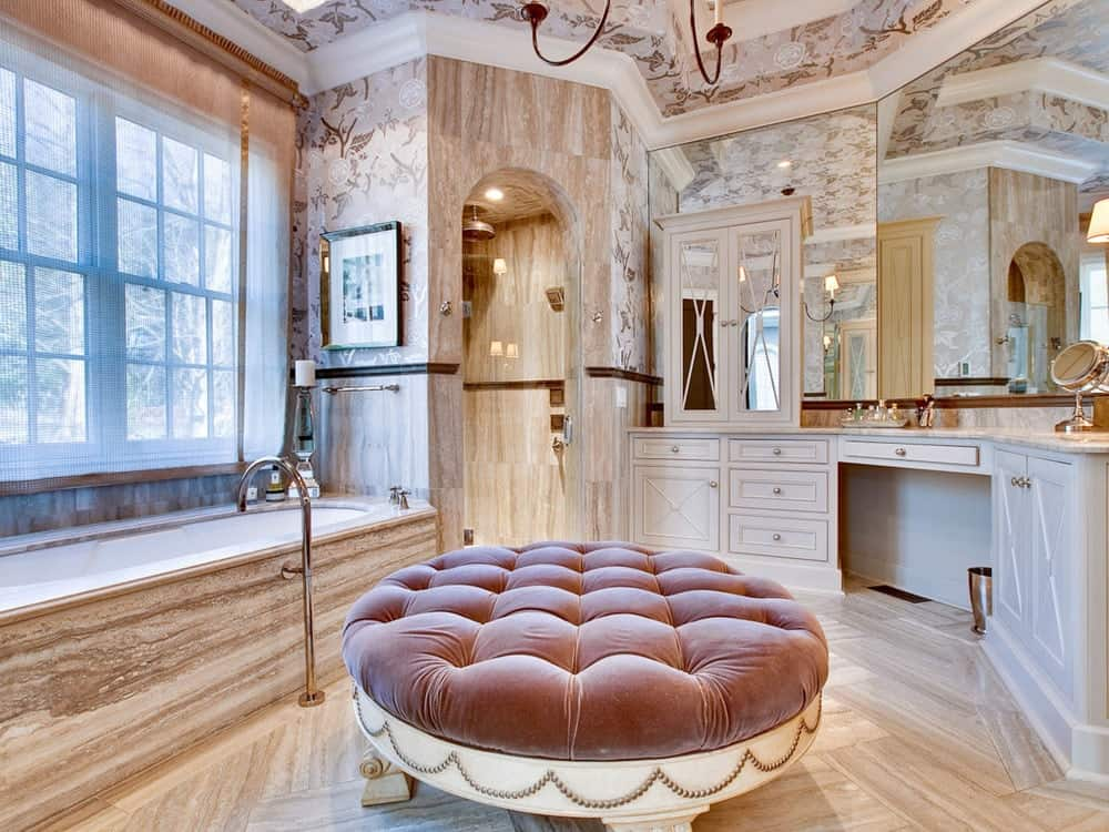 This luxurious bathroom has a large tufted ottoman chair beside the large bathtub under the curtained window. Beside this is the arched entrance of the walk-in shower area with the same beige tiles as the floor.