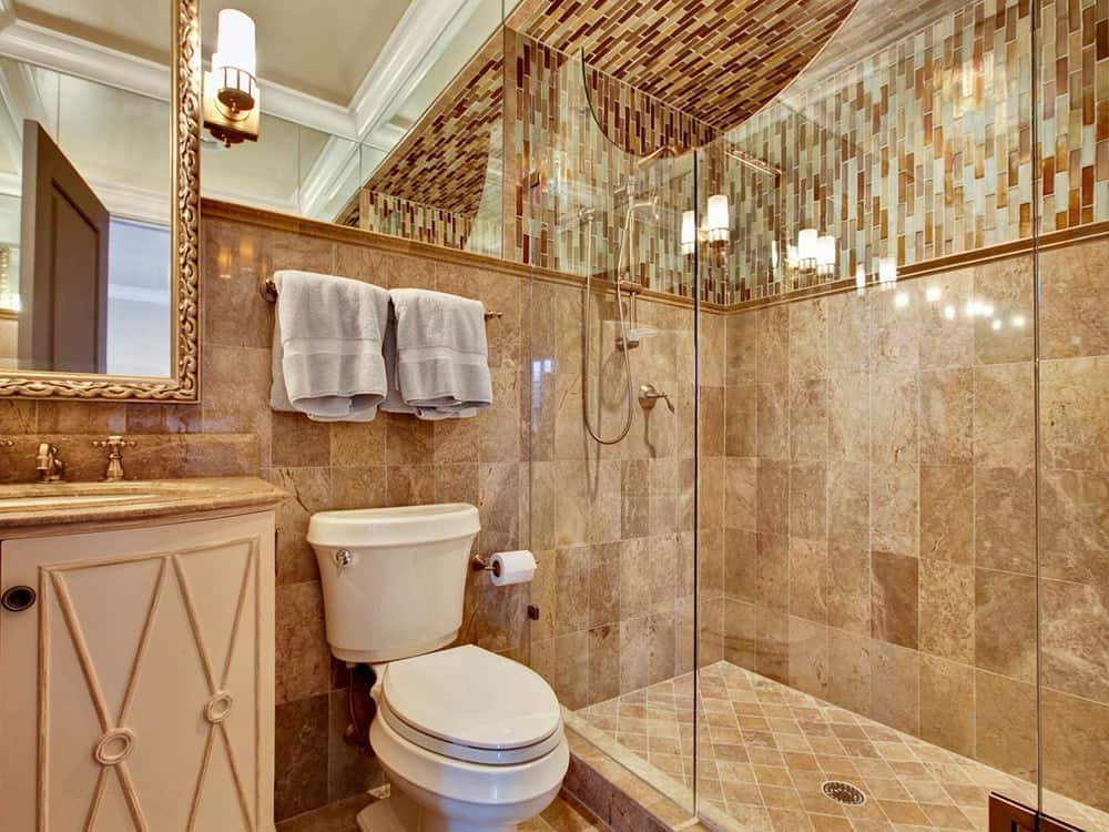 The toilet of this simple bathroom stands out against the earthy tones of the beige vanity on one side and the beige wall tiles of the glass-enclosed shower area on the other side.