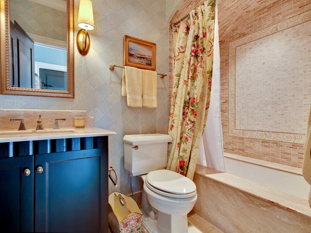 This is a homey bathroom with a matte dark vanity topped with a mirror. These are then complemented by the lovely floral shower curtain of the shower area beside the toilet.