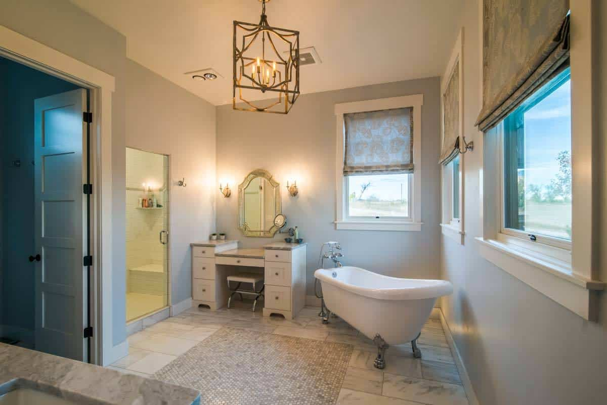 This primary bathroom has a lantern-like decorative semi-flush mount lighting in the middle of its ceiling. The freestanding bathtub at the corner by the windows is paired with a charming vanity area lit with warm yellow light from the wall-mounted lamps.