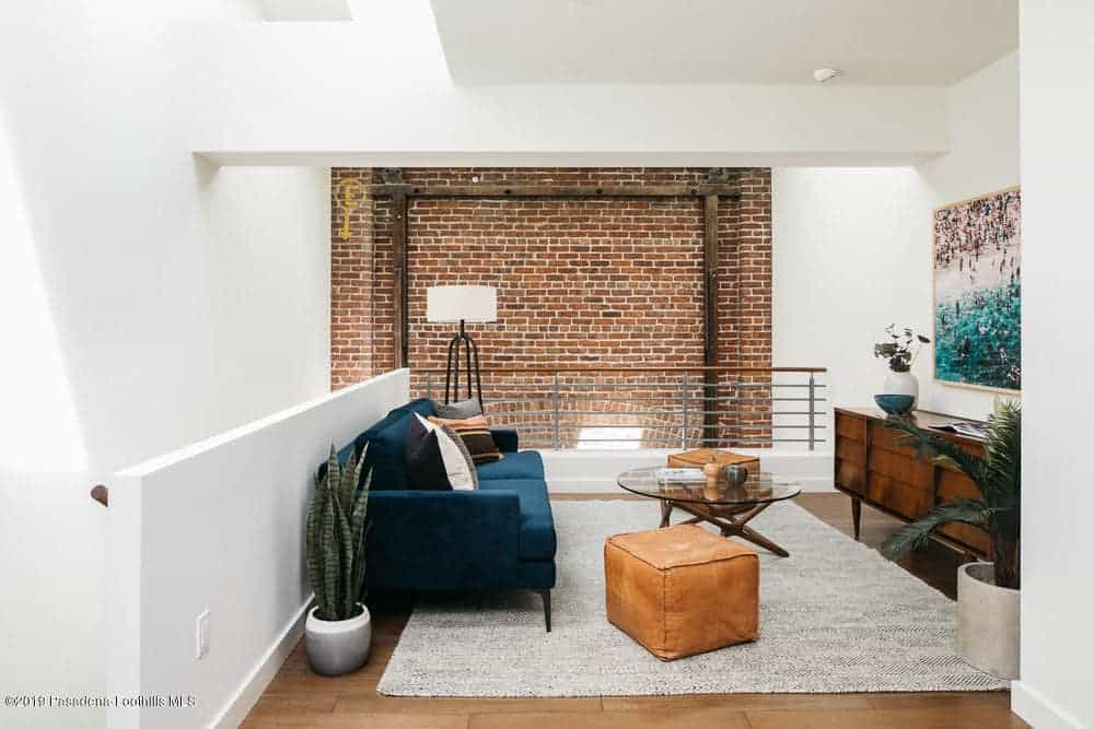 Industrial-style living interior with a view to the exposed brick wall, indoor plants, and an area rug over hardwood flooring.